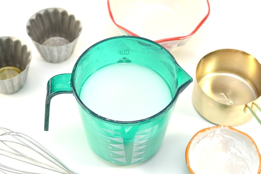 blue measuring cup with cloudy white glass cleaner mixture inside and measuring cups surrounding on white countertop