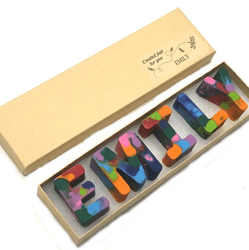 multicolored crayons in letters spelling out a name