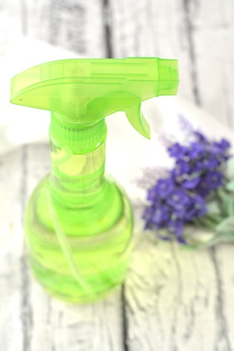 green spray bottle with lavender flowers on wood