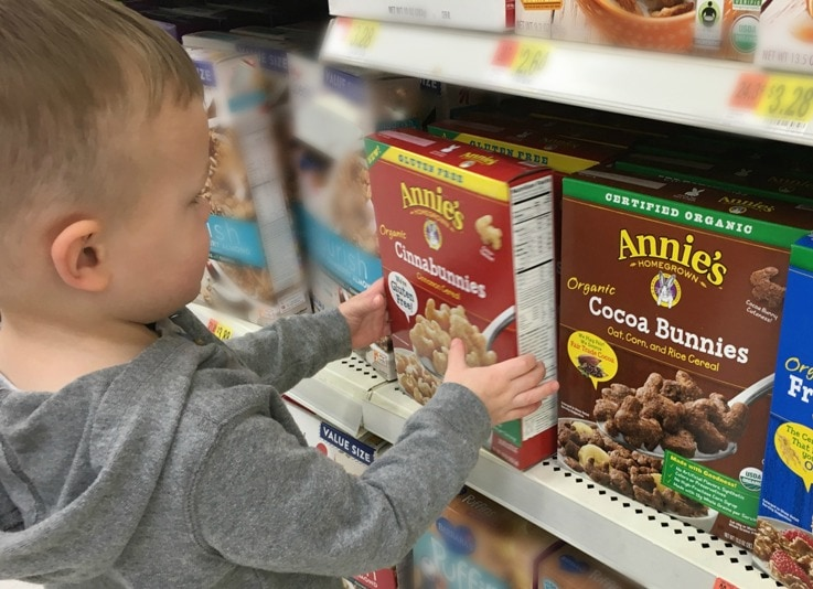 toddler boy grabbing a cereal box on store shelf