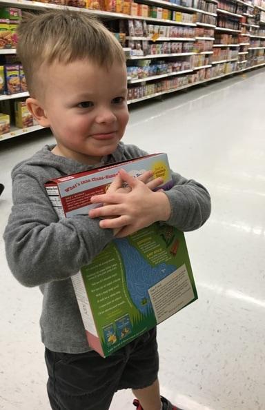 toddler boy hugging cereal box