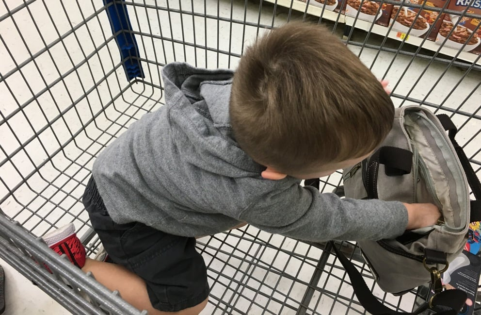 toddler digging through purse sitting in a shopping cart