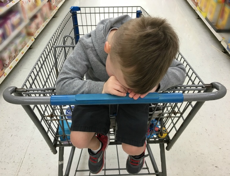 toddler pouting in shopping cart