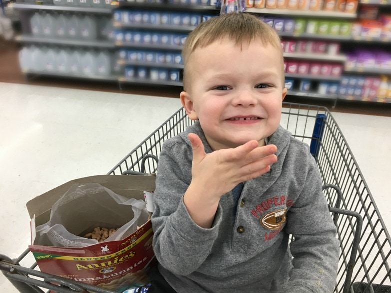 toddler boy smiling while eating cereal from a box while sitting in a shopping cart