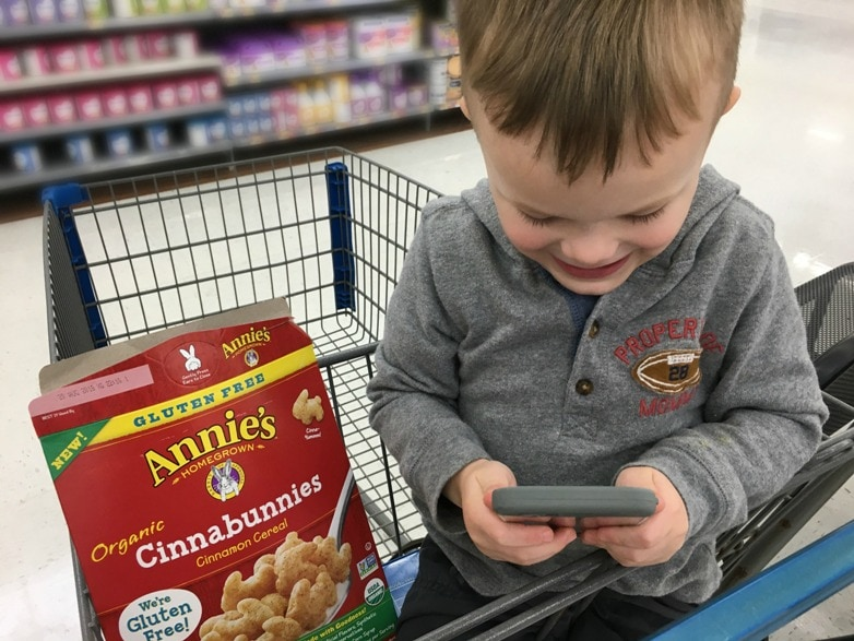 toddler playing on phone sitting in front seat of shopping cart with cereal box on the seat