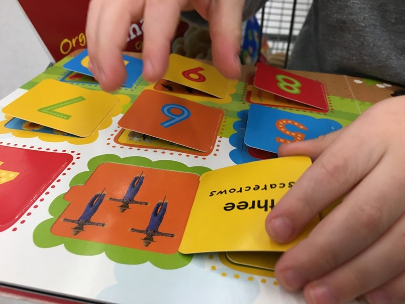 child's hands opening flaps in a popup book