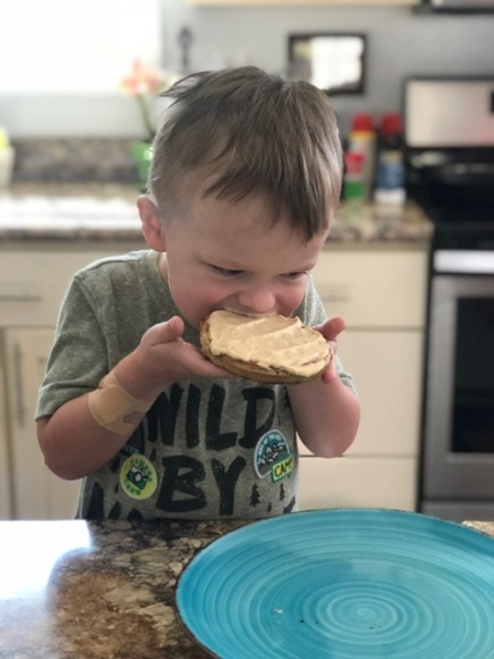 child eating waffle with hands
