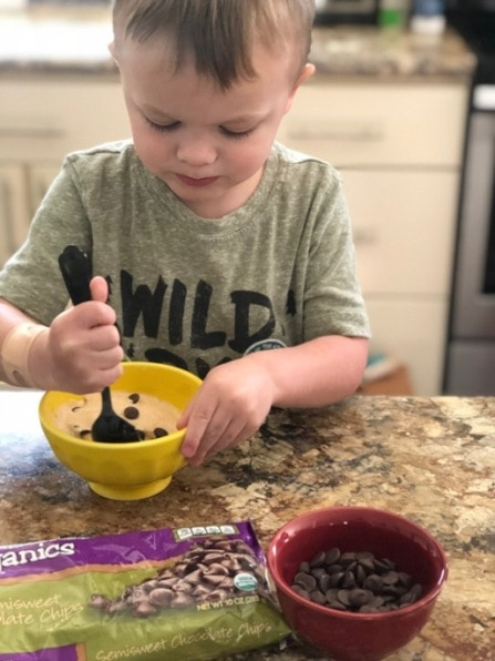 child stirring chocolate chips into a bowl