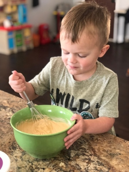 child stirring food in a bowl with a whisk