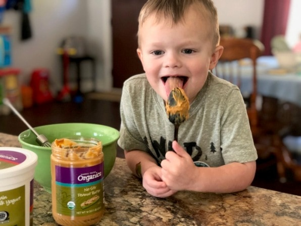 child licking a spoon with peanut butter
