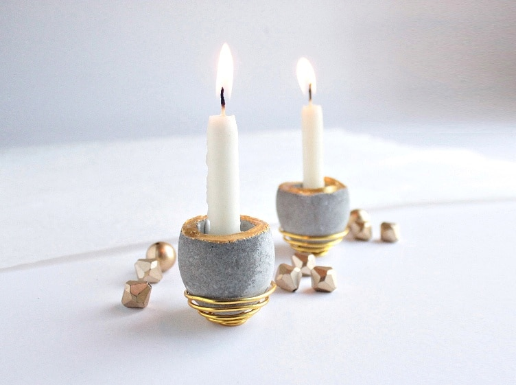 Candles burning in mini concrete candleholders shape of an egg
