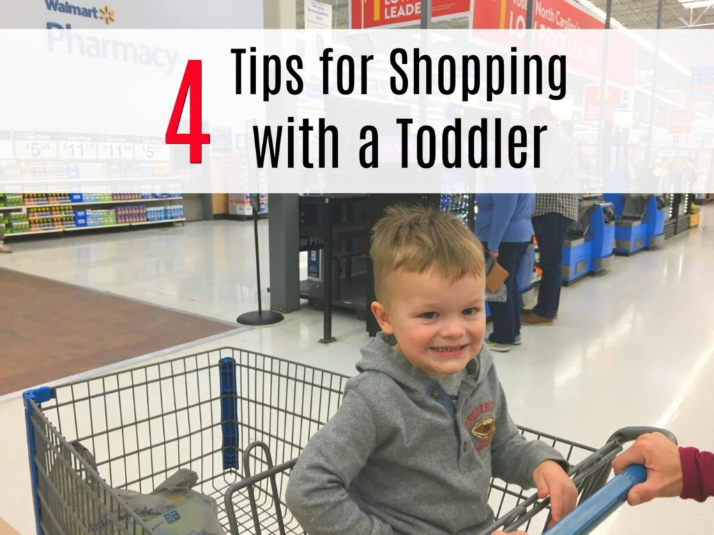 toddler boy sitting in front seat of shopping cart smiling