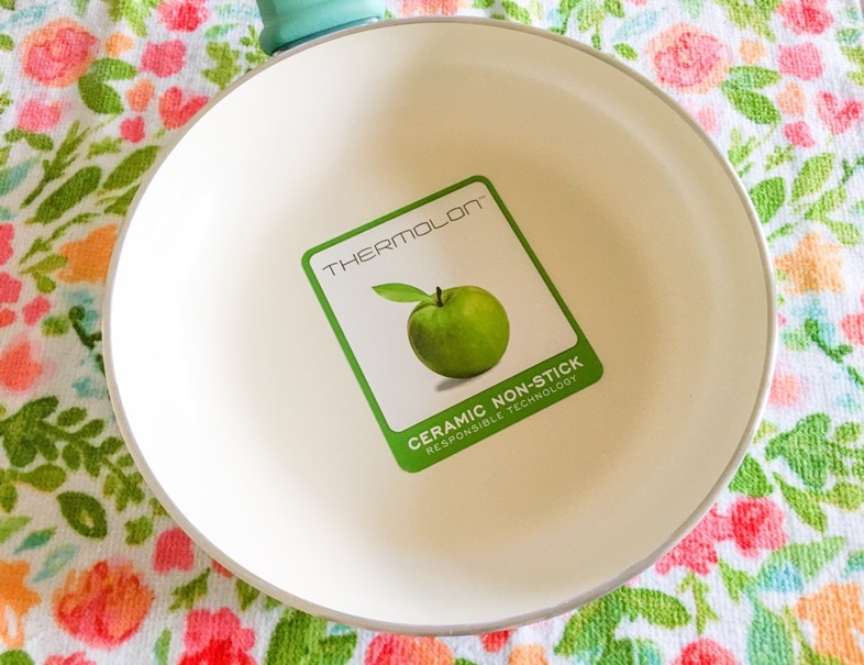 thermolon sticker with green apple on nonstick ceramic cookware pan against colorful flower towel