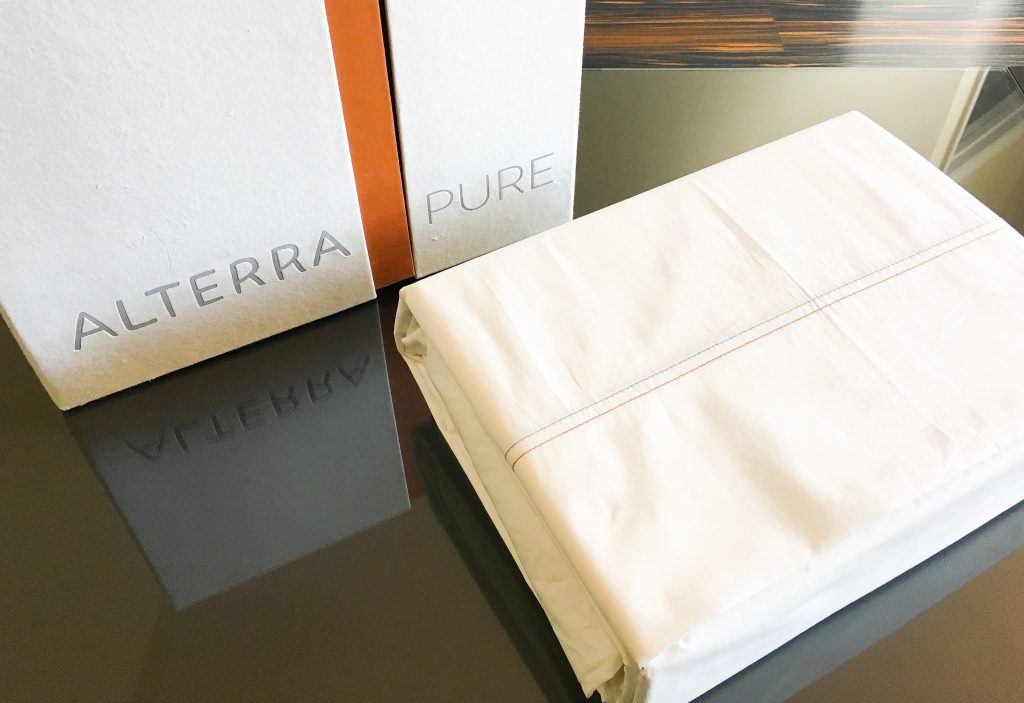 organic off-white cotton sheet set with recycled paper box on a glass table