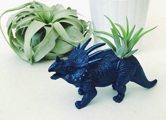 bright metallic blue dinosaur with air plant planted in back with succulent in the background