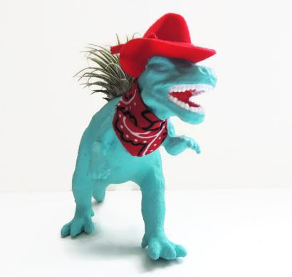 blue plastic dinosaur dressed up like a cowboy with a red hat and a red bandana and air plant growing in back