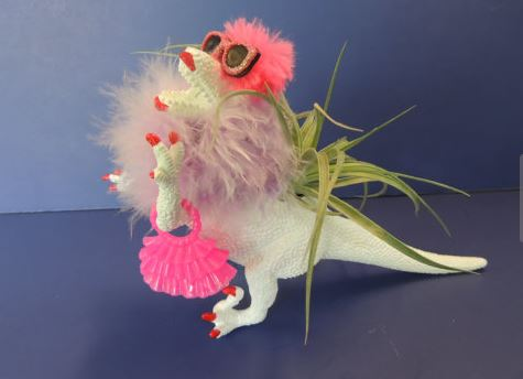 white plastic dinosaur wearing a purple feather boa pink sunglasses purse and red painted nails