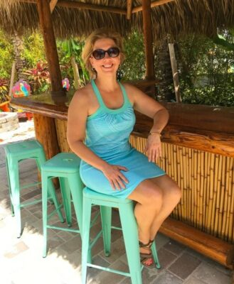 woman sitting down on a teal metal stool wearing teal dress by tiki bar