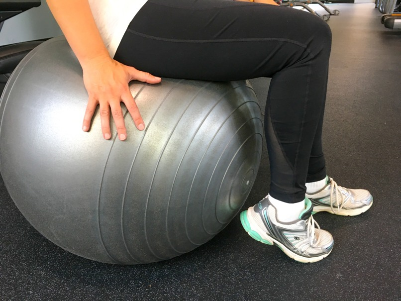 sitting on grey workout ball wearing black leggings