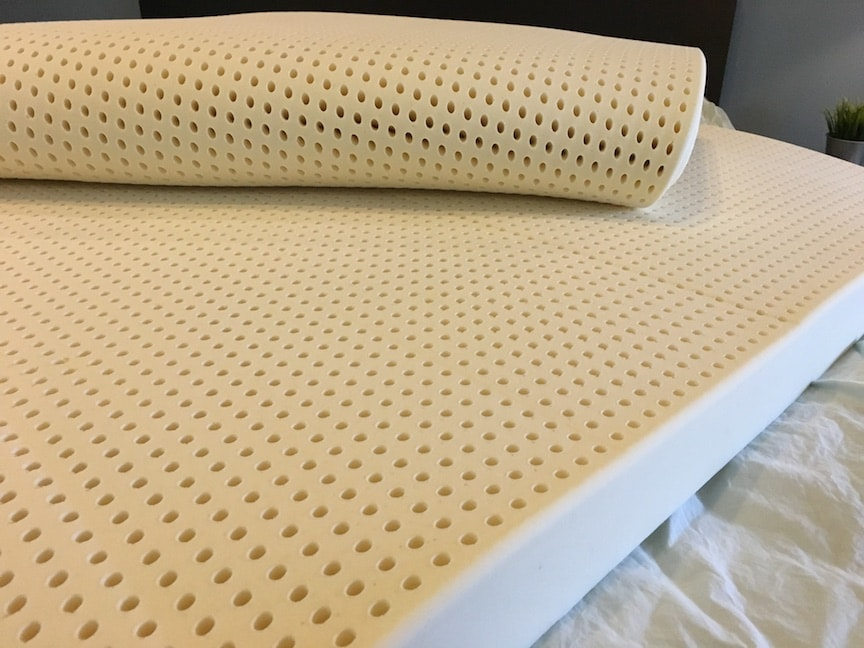 Latex for Less Mattress Topper unrolled on a bed