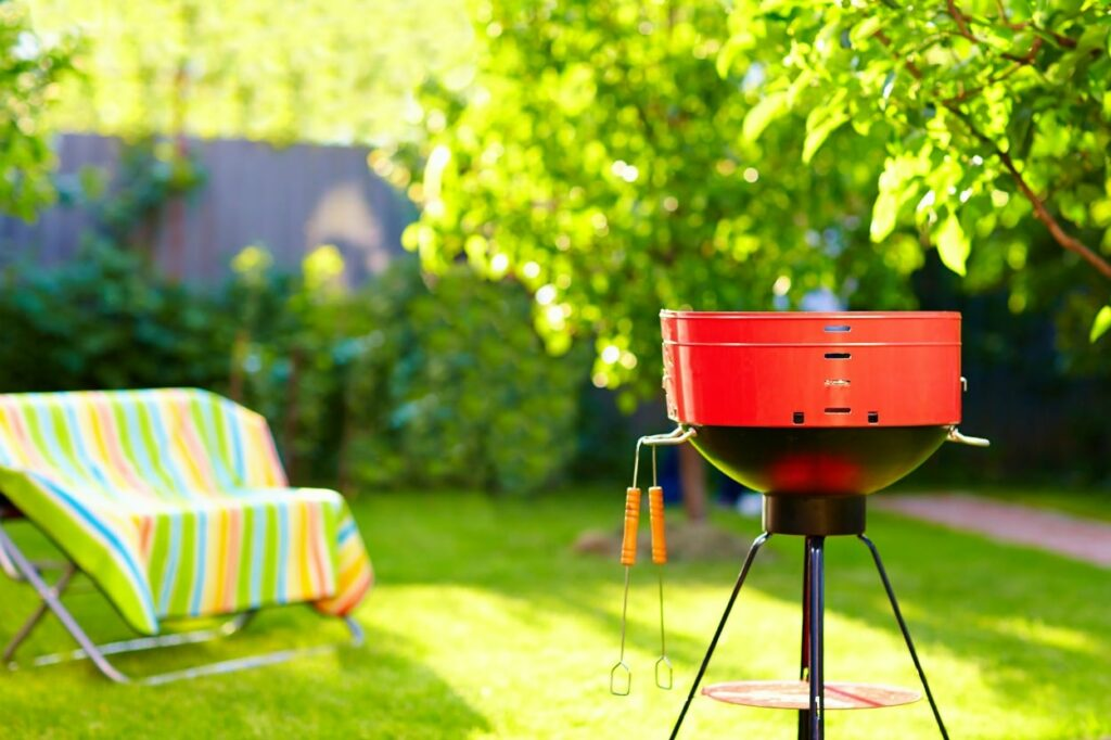 red bbq grill in backyard with green grass and trees and colorful striped chair