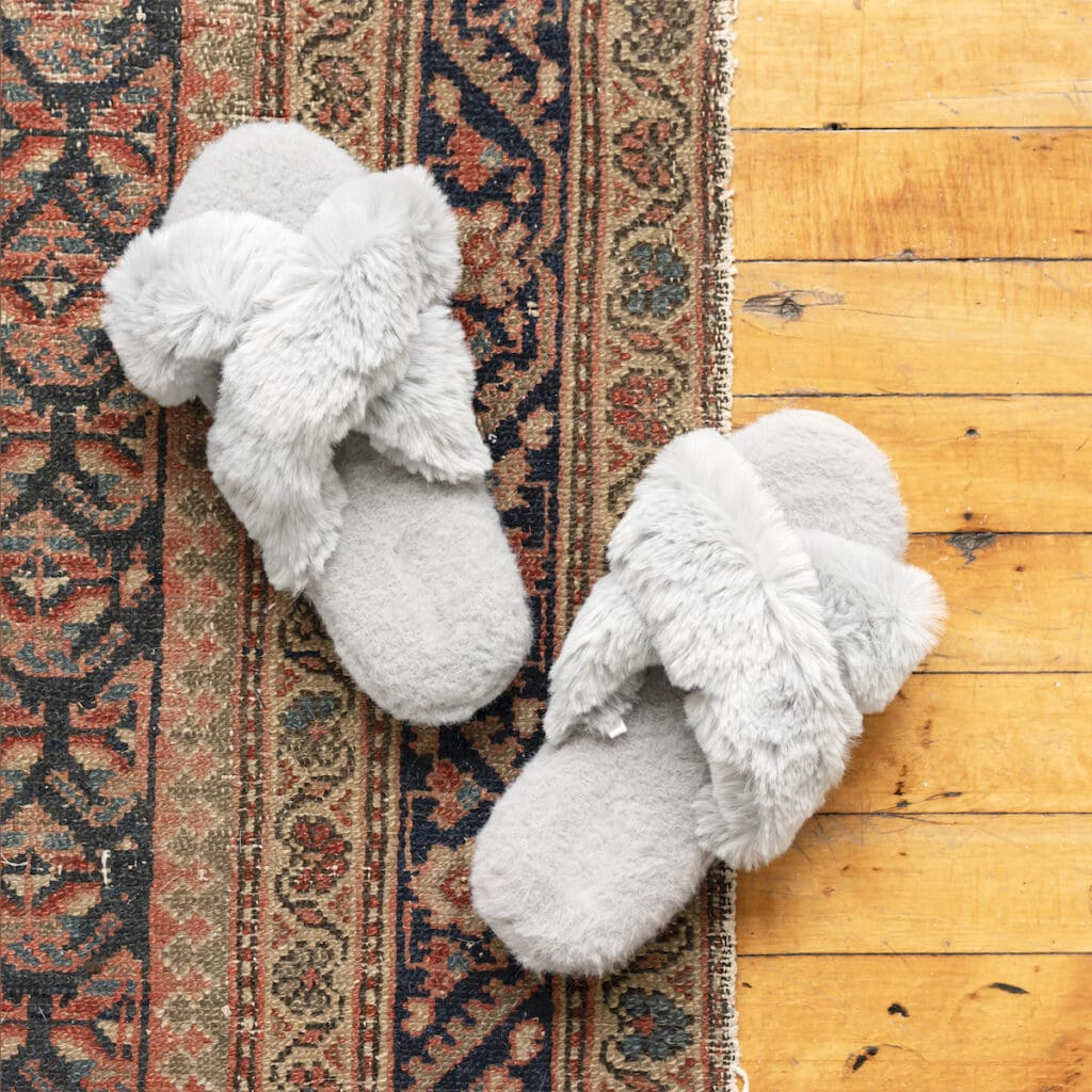 throw rug on wooden floor with grey fuzzy slippers