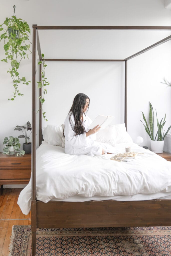 Woman sitting on mattress in bedroom