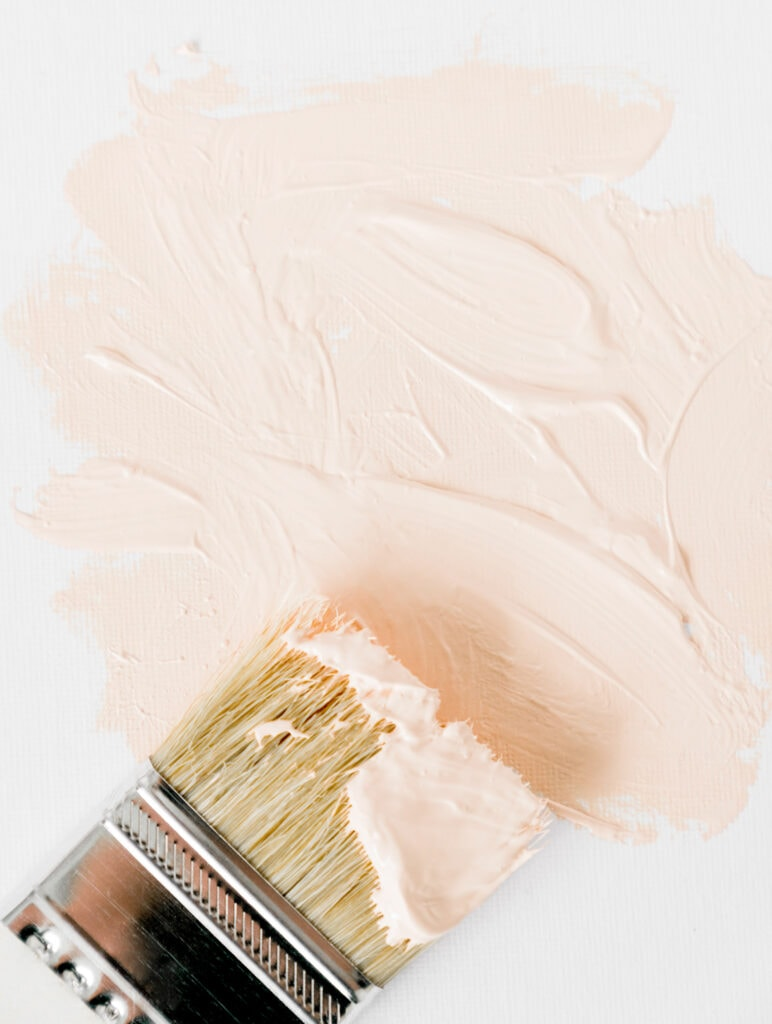 paint brush and pink paint on white wall