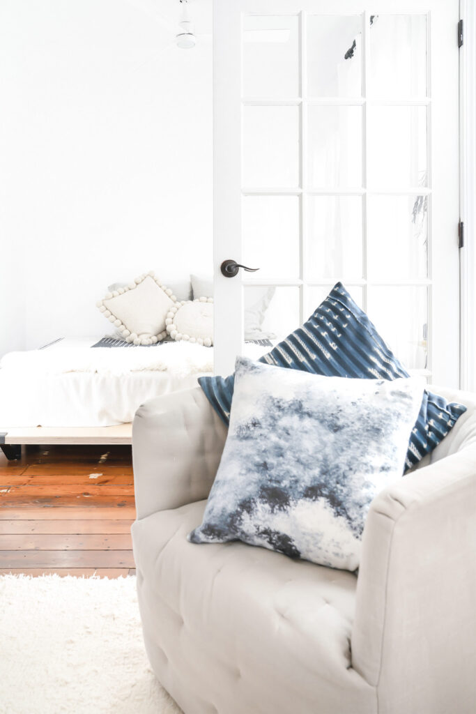 tan upholstered chair with blue throw pillows on white carpet