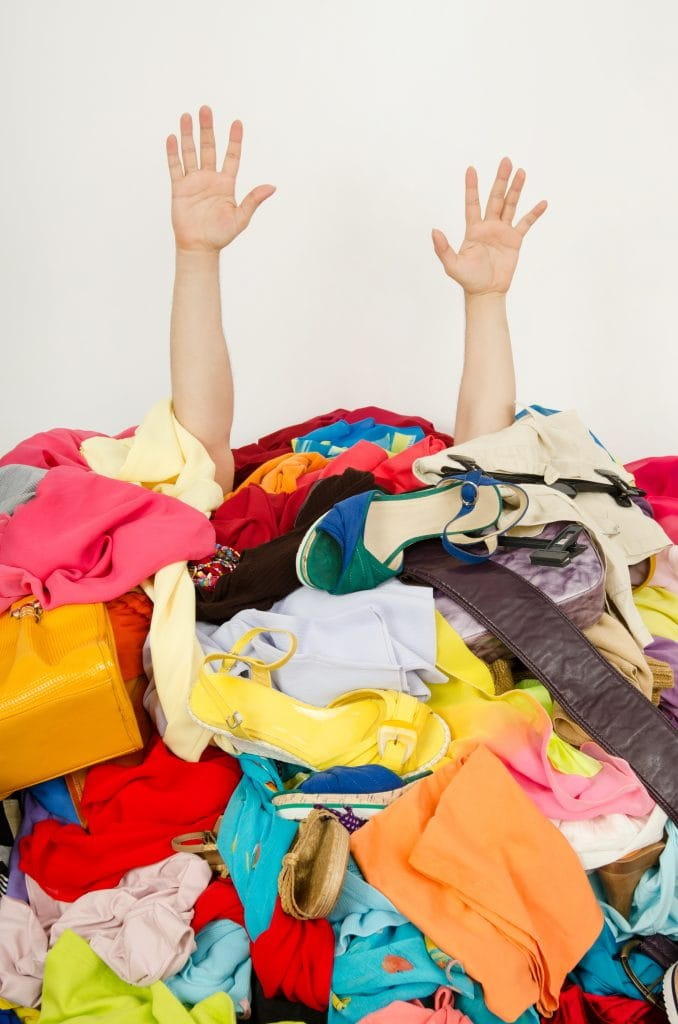 woman under a pile of clothes and shoes with hands up in the air