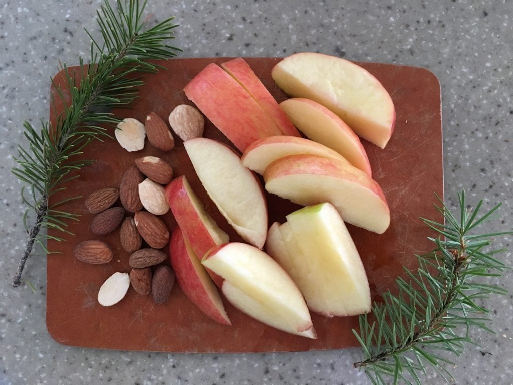 cutting board with apples almonds and pine branches
