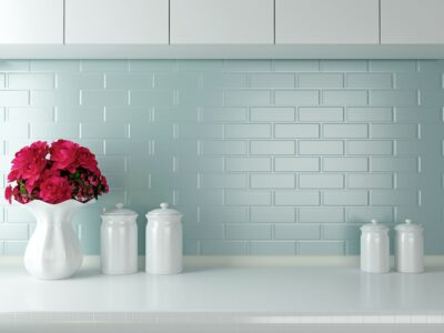 blue backsplash with white counters and white vase filled with pink flowers