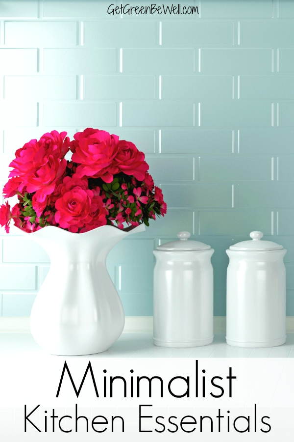 minimalist kitchen essentials on white countertop with vase of pink flowers
