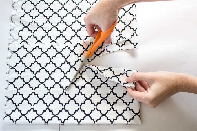 Scissors cutting fabric in circle against white background