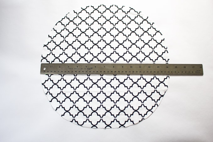 black and white geometric print fabric cut in a circle with a ruler laying across against white background