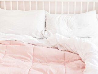 comfy bed with white sheets and pink duvet cover against white wood headboard