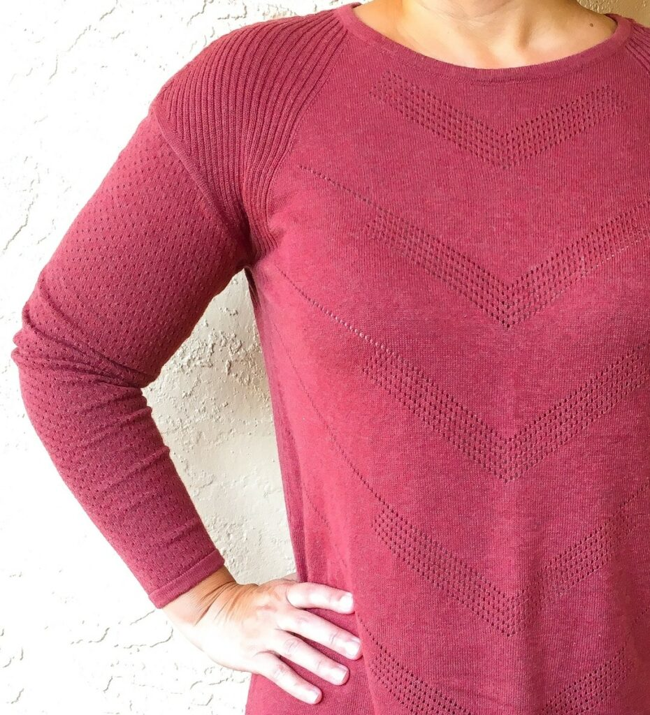 wine colored sweater against cream colored wall