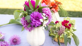 purple and orange flowers with greenery in white pumpkin flower vase on table