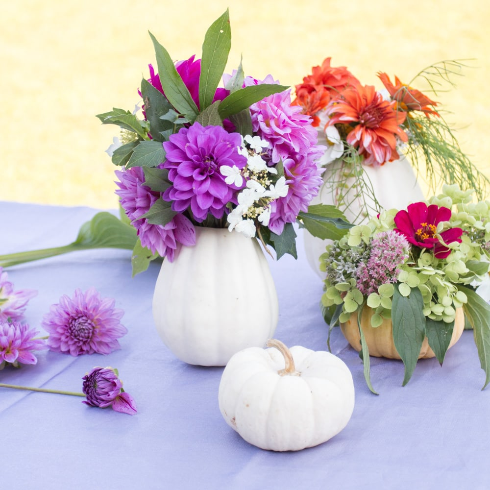 white pumpkin flower vases filled with purple flowers and greenery