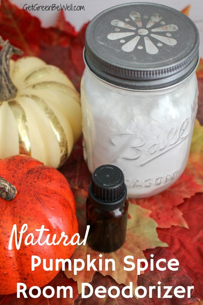 Glass jar with white baking soda against pumpkins, white wood background, fall leaves and essential oil bottle