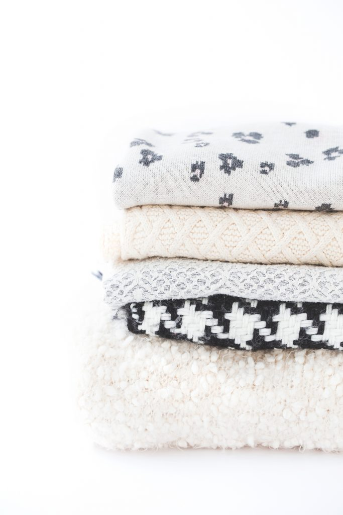 cozy grey, white, and black blankets stacked up against a white background