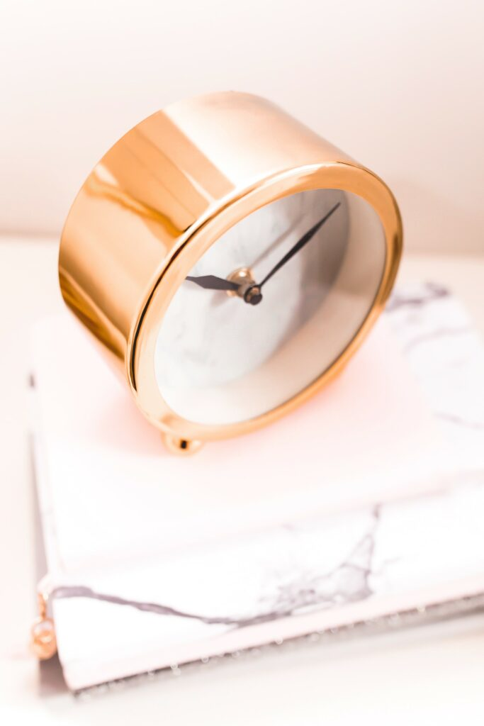 gold round battery powered alarm clock on marble table