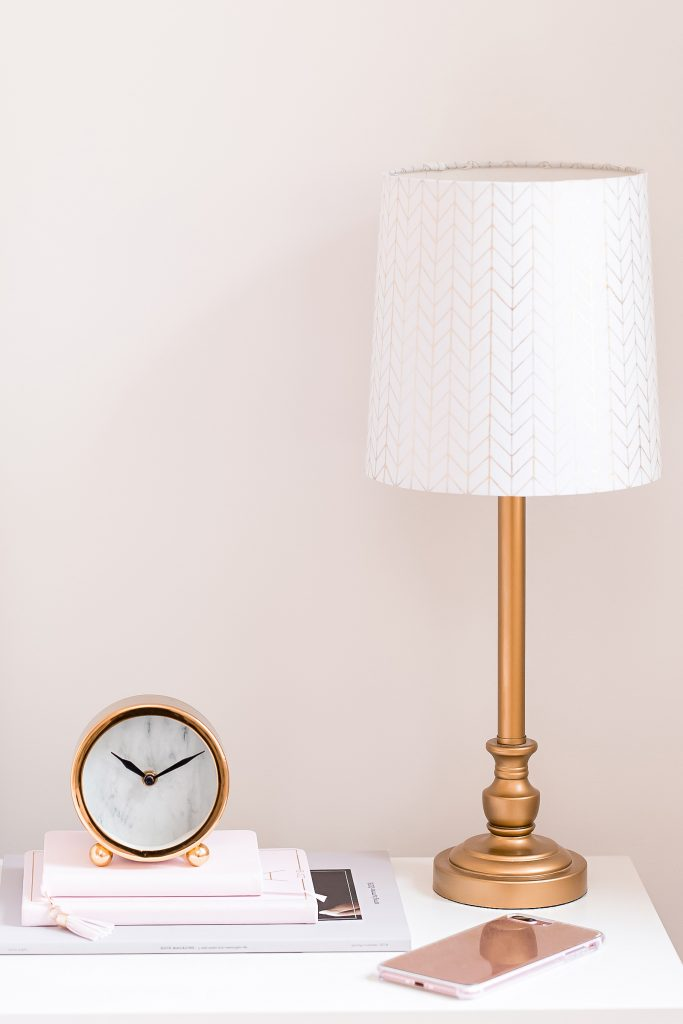nightstand with gold lamp and battery operated clock on books against pink wall