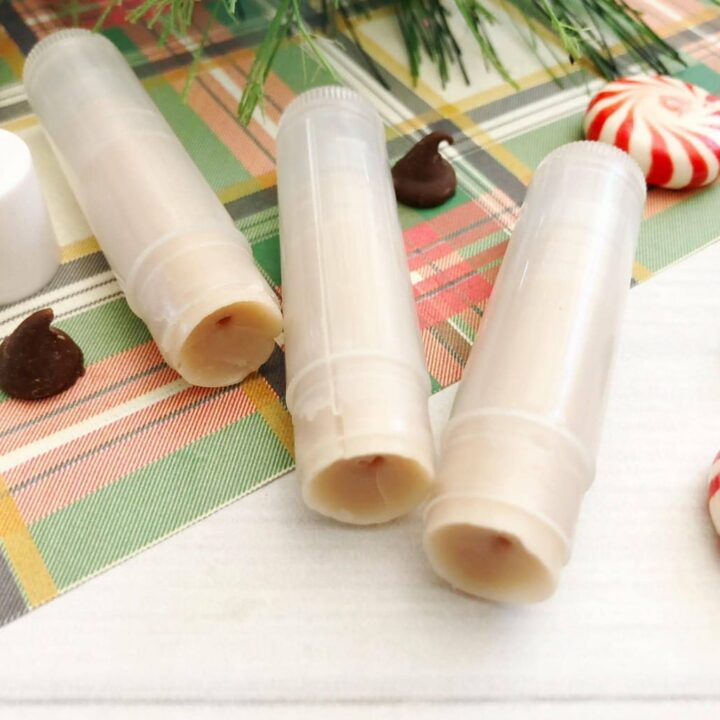 lip balm tubes on table with chocolate chips and peppermint candies