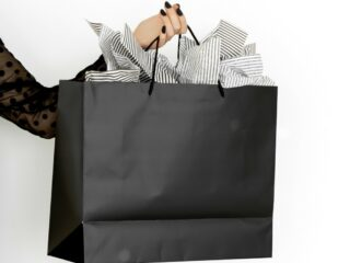 woman in black dress holding black shopping bag for Black Friday sales
