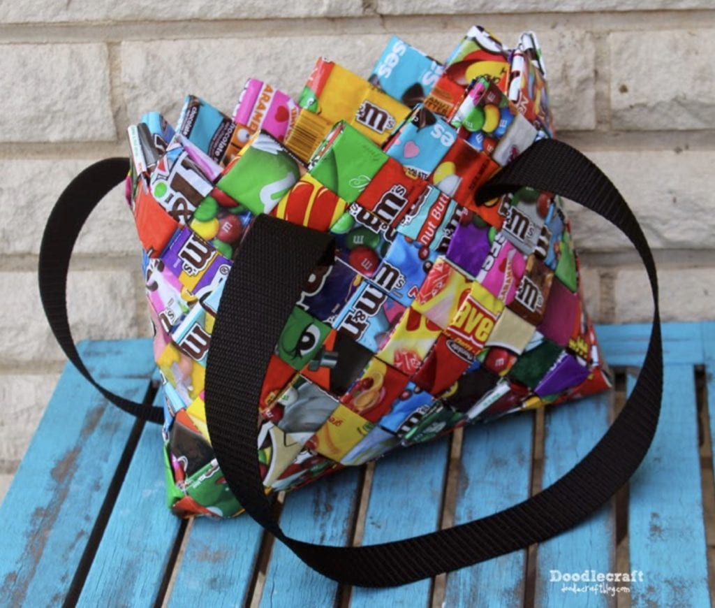purse made out of candy wrappers with black handles on blue table