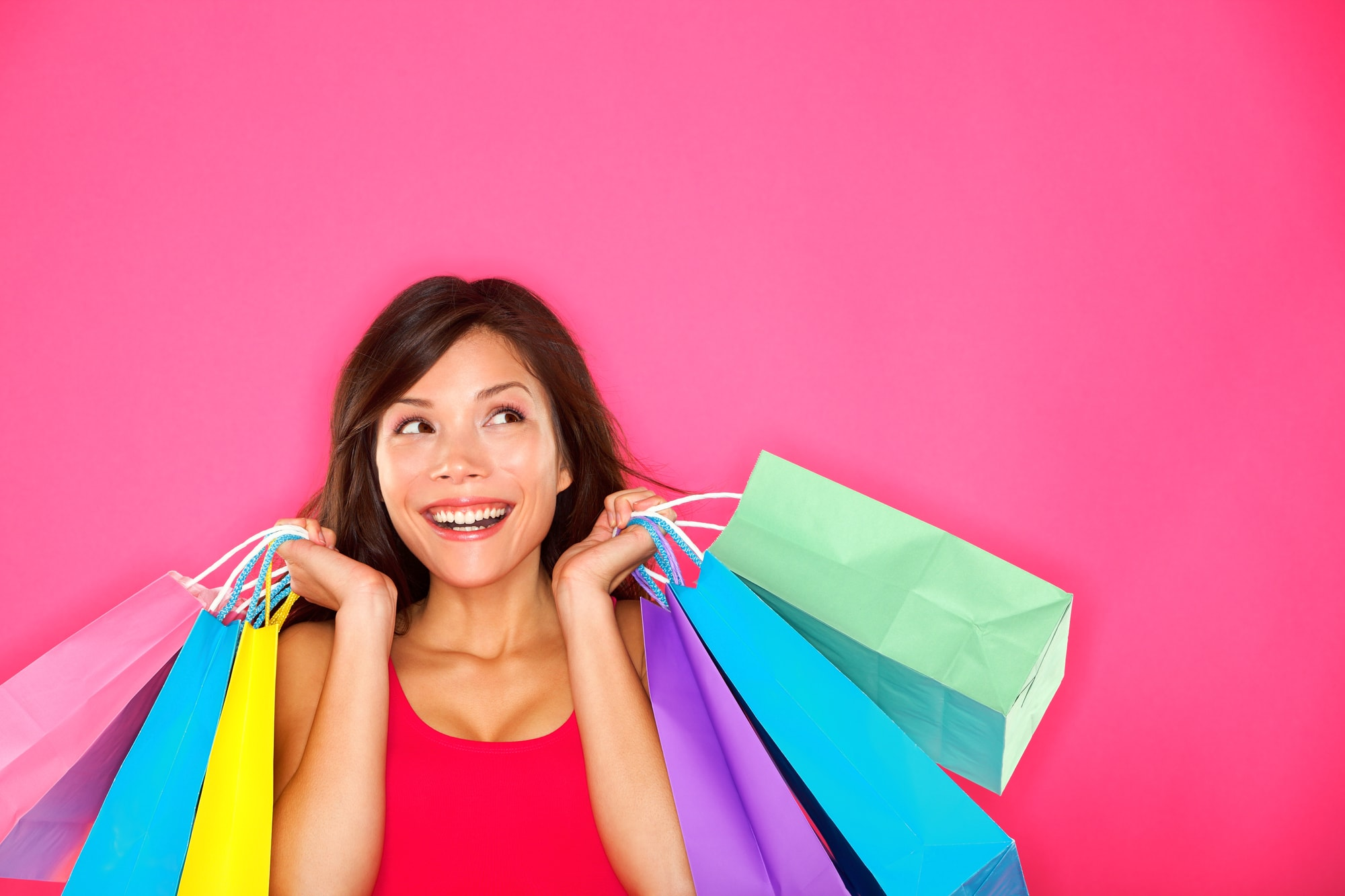 woman with shopping bags against pink background
