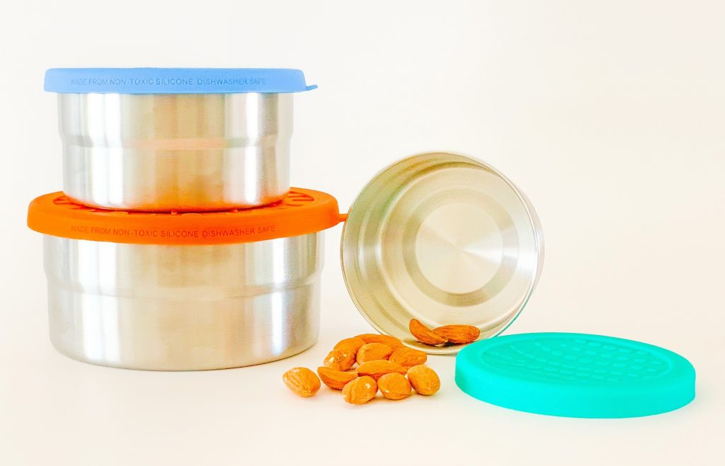 three stainless steel storage containers with blue, orange and teal colored silicone lids and almonds on white background