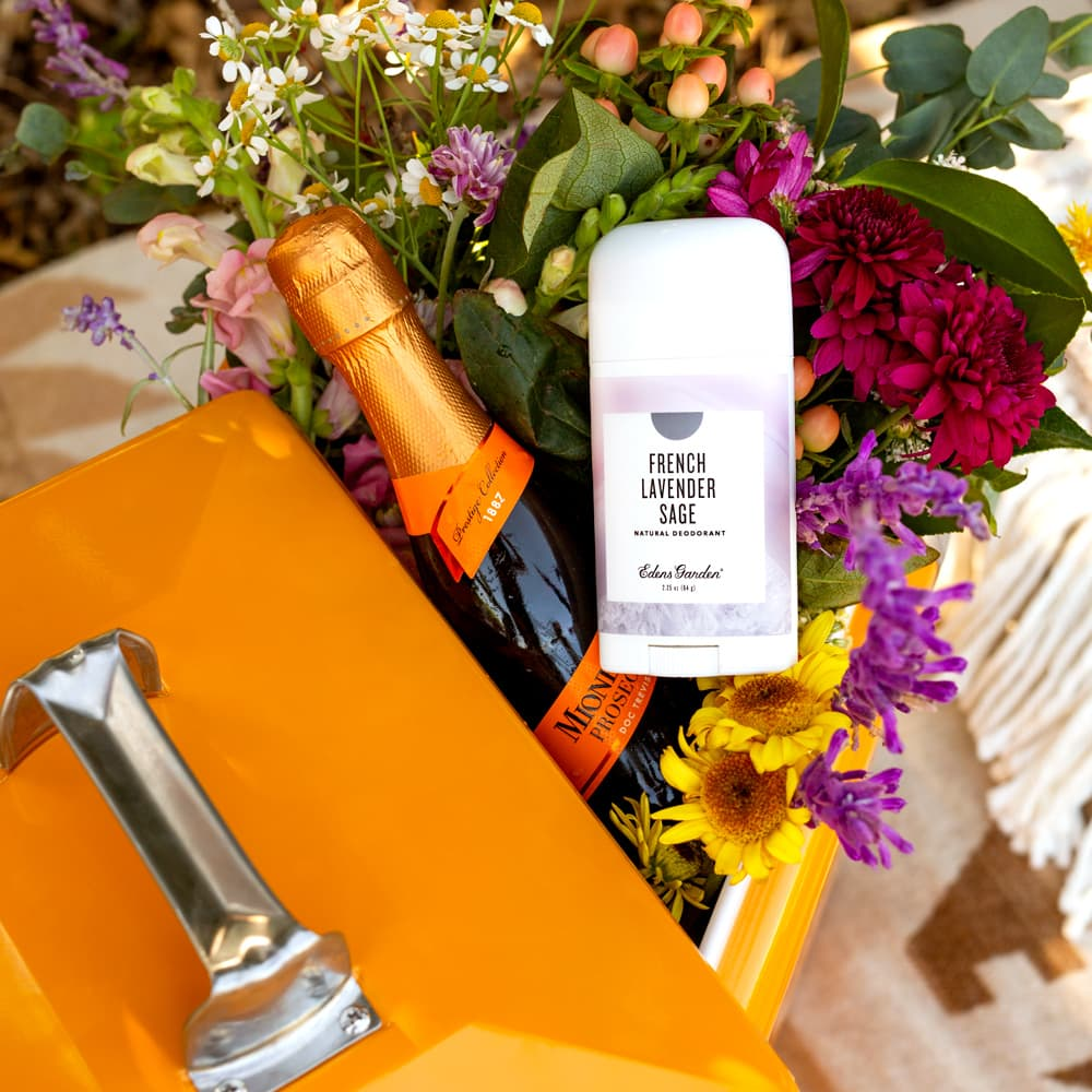 natural deodorant laying on flower bouquet with champagne bottle