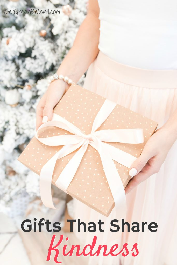 woman in pink skirt holding brown wrapped gift with pink bow against Christmas tree covered in white snow